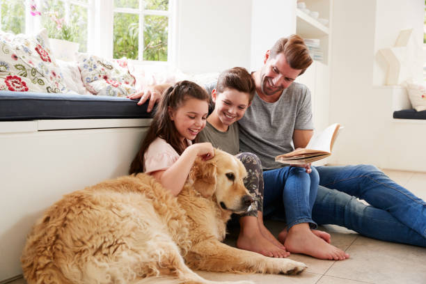 father reading book with son and daughter and pet dog at home - canide foto e immagini stock