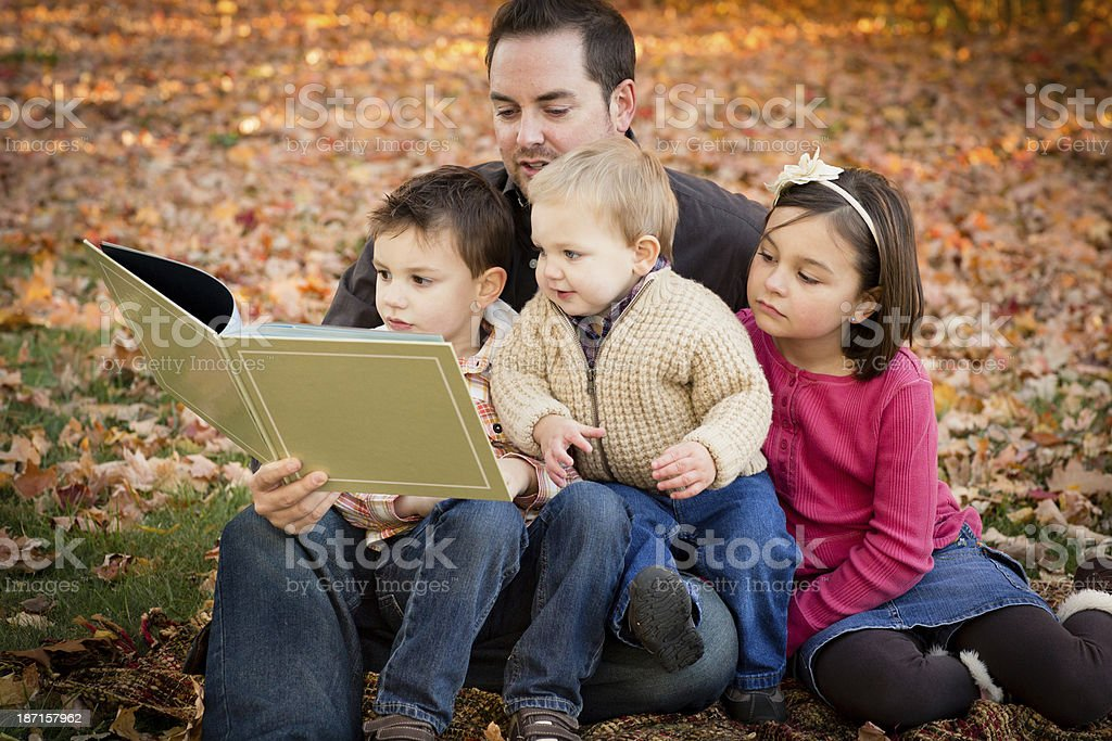 Father Reading to His Children Outdoors on Fall Day stock photo