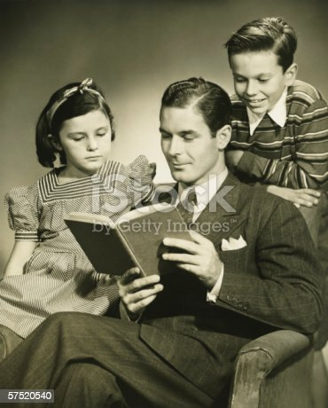 57520540 istock photo Father reading to son (4-5) and daughter ( 6-7) in studio, (B&W), portrait 57520540