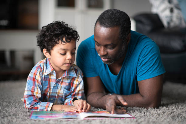 Father reading to son A young father of African descent is lying on the carpet in their living room and reading to his son. reading stock pictures, royalty-free photos & images