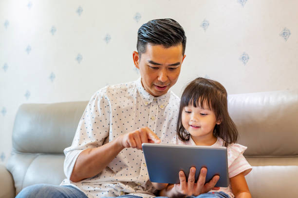 Father Reading With His Toddler Daughter on a Tablet Computer stock photo