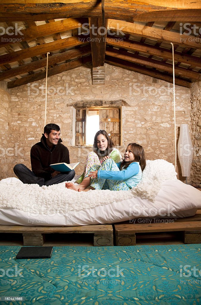 Father reads a story to her daugthers in bed. royalty-free stock photo