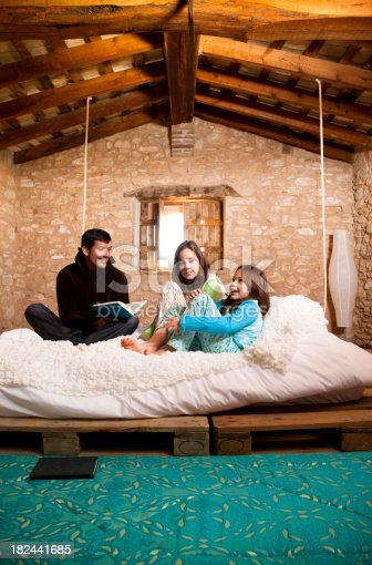 57520540 istock photo Father reads a story to her daugthers in bed. 182441685