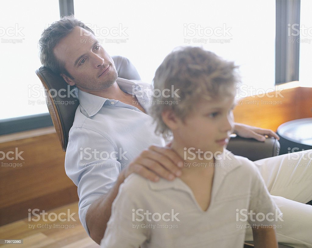 Father relaxing with hand on son's shoulder at home royalty-free stock photo
