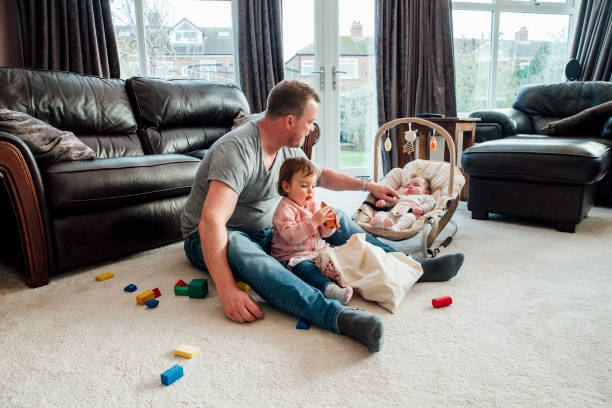 Father Relaxing with his Daughters at Home Stay at home father with his daughters at home. The eldest girl is sitting with her father playing with toy dinosaurs while the baby girl is in her rocker chair next to them. stay at home father stock pictures, royalty-free photos & images