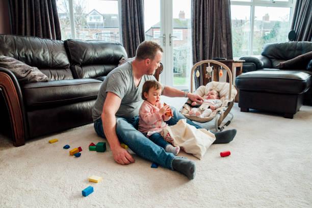 relajante de padre con sus hijas en casa - padre que se queda en casa fotografías e imágenes de stock