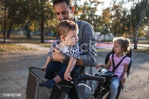 Close up of Father riding a bicycle with his kids on a baby seat