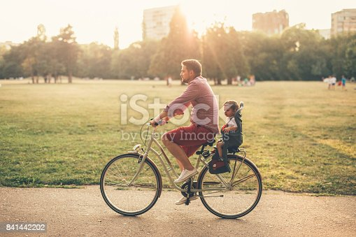 istock Father riding a bicycle with his son on a baby seat 841442202
