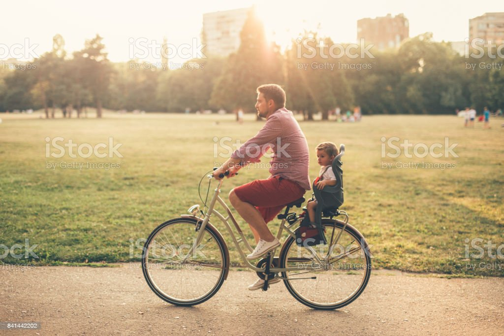 Father riding a bicycle with his son on a baby seat stock photo