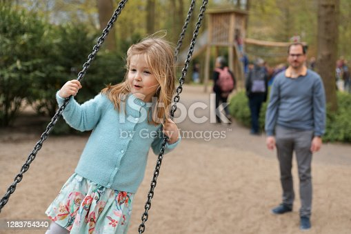 Father rolls daughter on a swing at a park