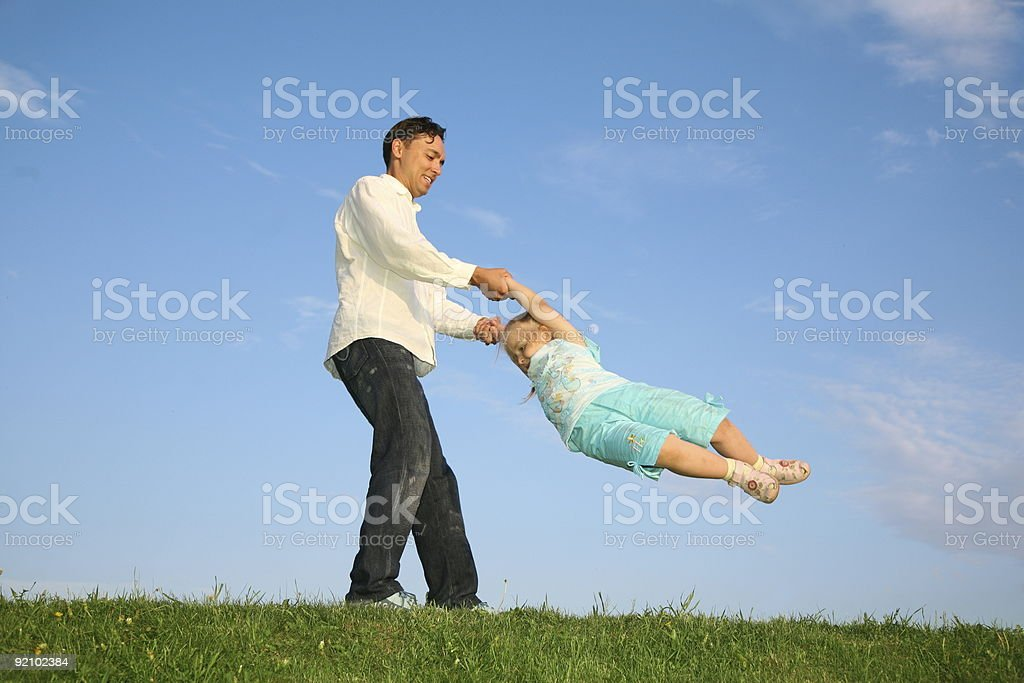 father rotates daughter royalty-free stock photo