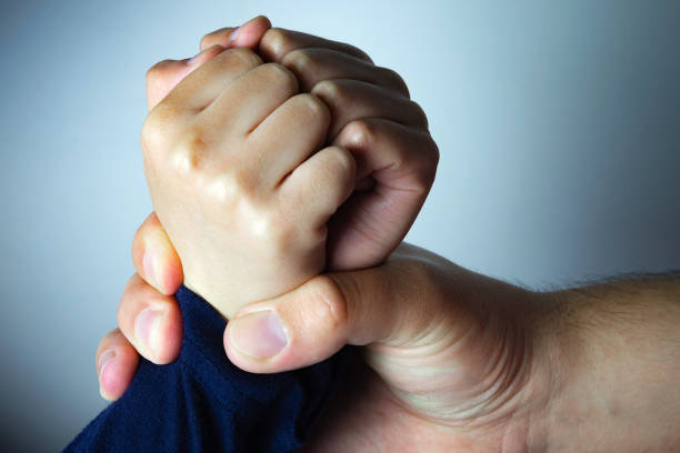 Father roughly holds the hands of his son. Child abuse, domestic violence. Father roughly holds the hands of his son. Child abuse, domestic violence. Concept image. daunt stock pictures, royalty-free photos & images
