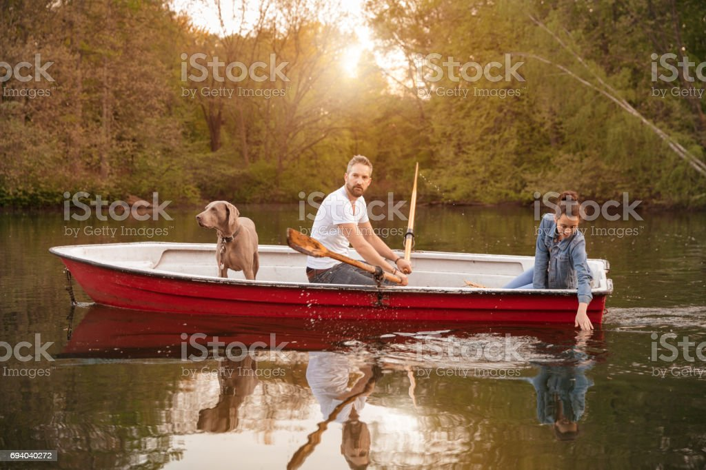 Father rowing boat with daughter and Weimaraner on lake against trees stock photo