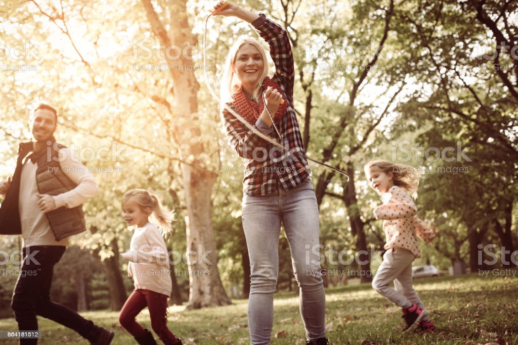 Father running with daughters trough park and mother holding jump rope. royalty-free stock photo