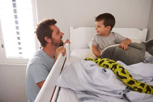 father saying goodnight to son at bedtime - etagenbett weiss stock-fotos und bilder