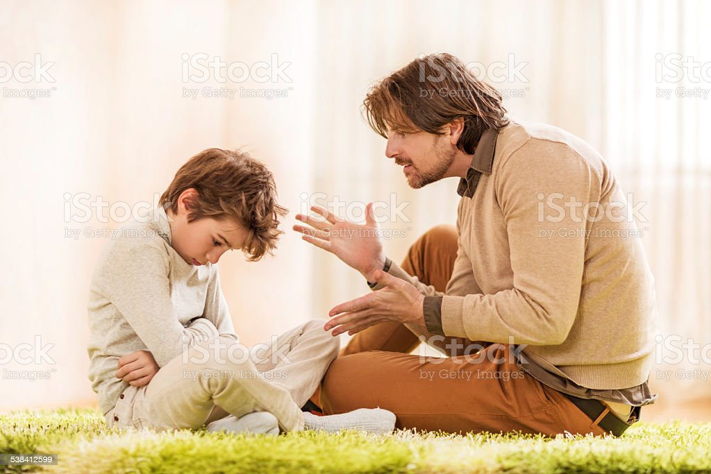 Father scolding his son. stock photo