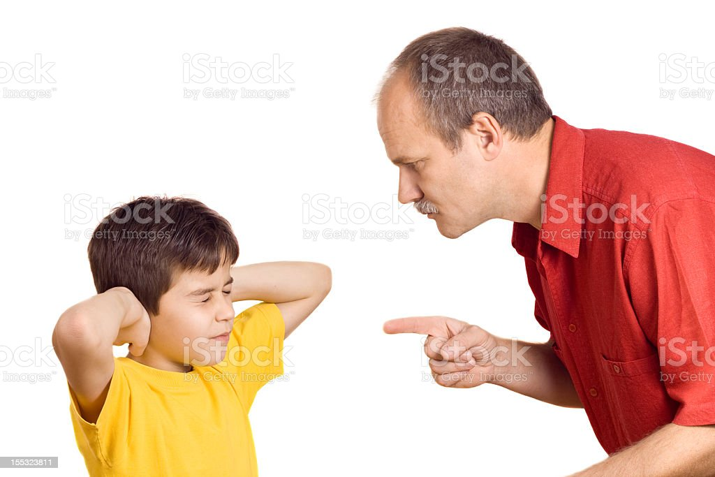 A father scolding his son who is covering his ears stock photo