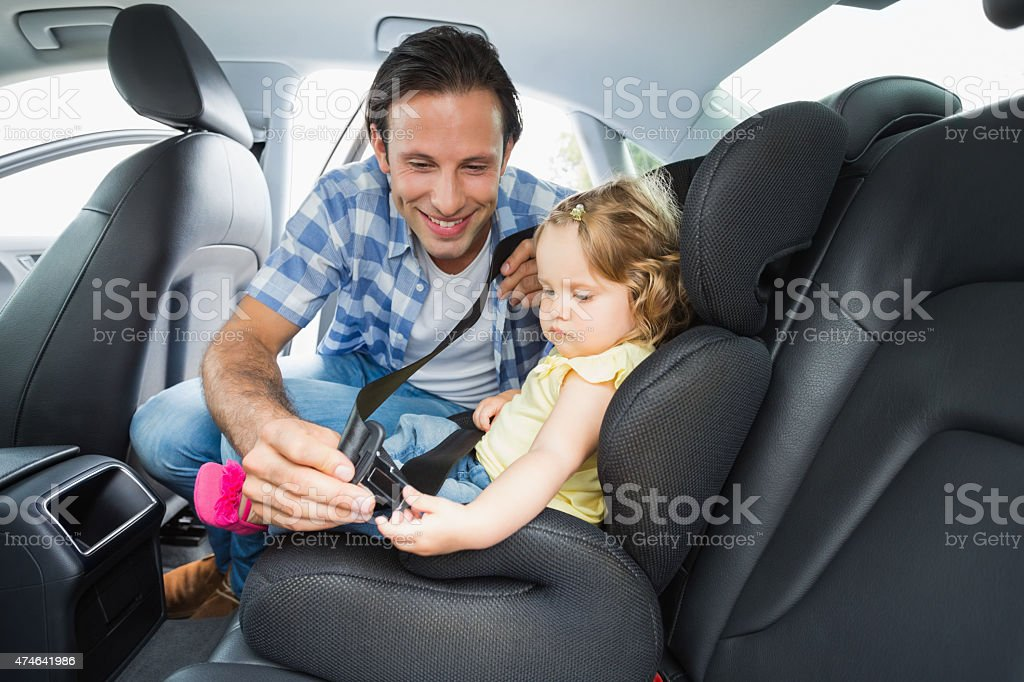Father securing baby in the car seat stock photo