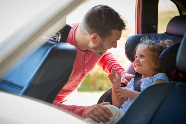 Father Securing Daughter Into Rear Child Seat Before Car Journey stock photo