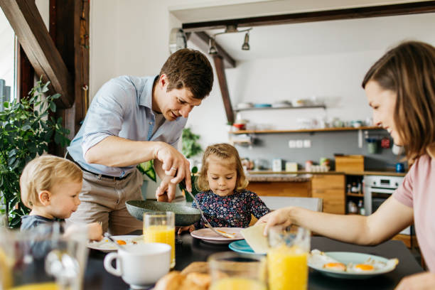 padre sirviendo el desayuno a la familia - desayuno fotografías e imágenes de stock