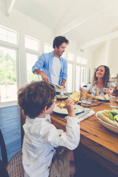 Father serving food to his family. stock photo