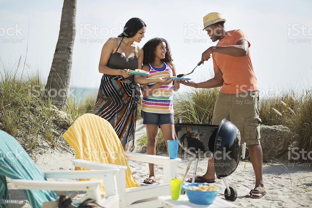 Father Serving Grilled Food To Family On Beach stock photo