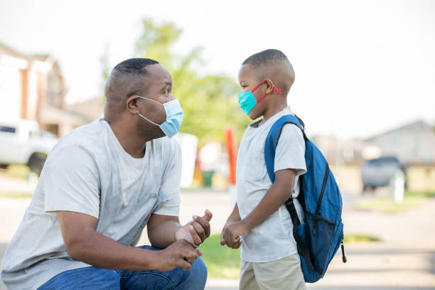Father sharing wisdom with son on the first day of school stock photo