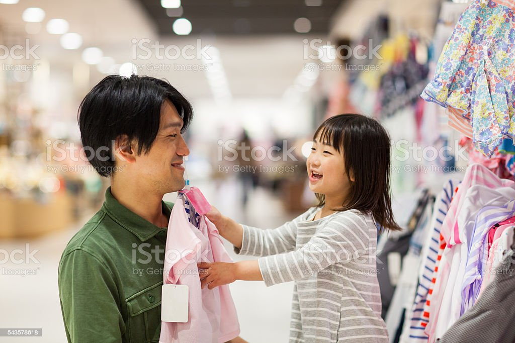 Father shopping for a dress with his young daughter stock photo