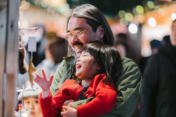 vater mit seinen beiden töchtern einkaufen - weihnachten japan stock-fotos und bilder