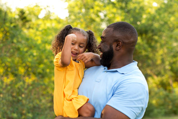 Father showing his daugher how to flex her muscles. Family having fun playing outside. flexing muscles stock pictures, royalty-free photos & images