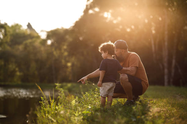 Father showing lake to his son stock photo
