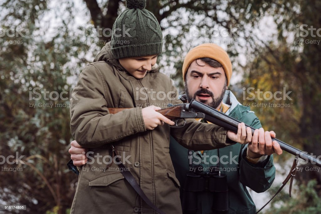 Father showing son how to load gun stock photo