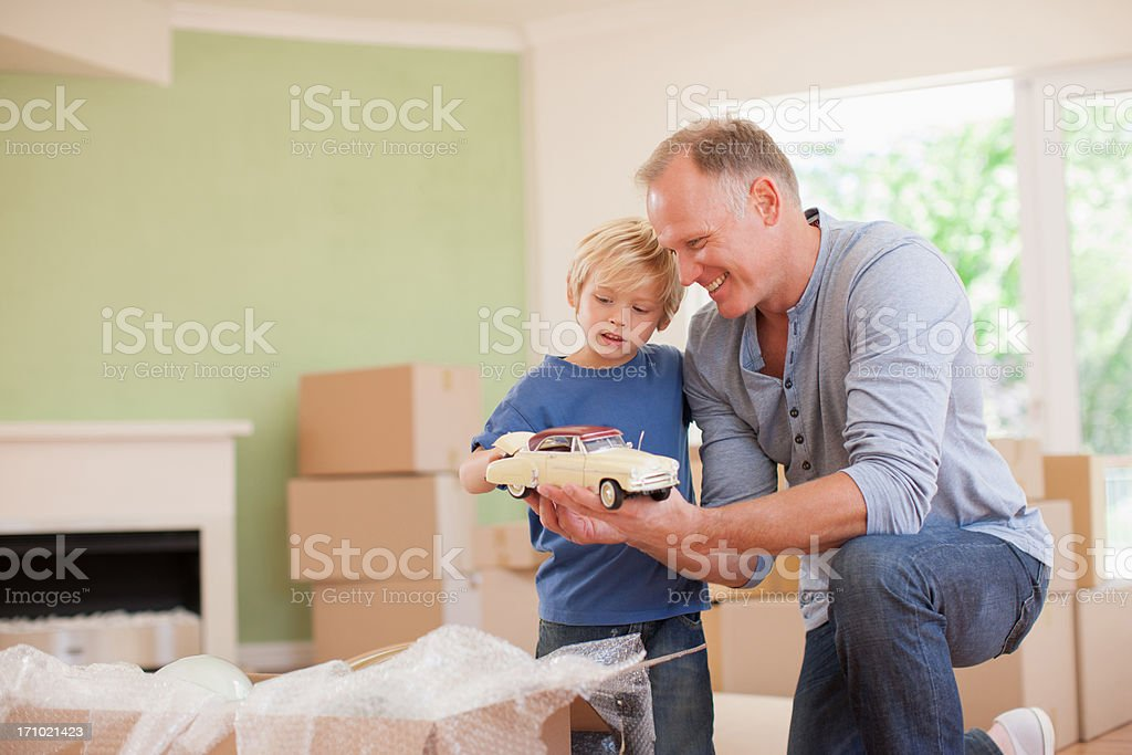 Father showing son model car in new house stock photo