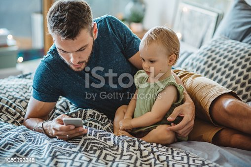 Father and daughter having fun at home. They play on bed and using phone.