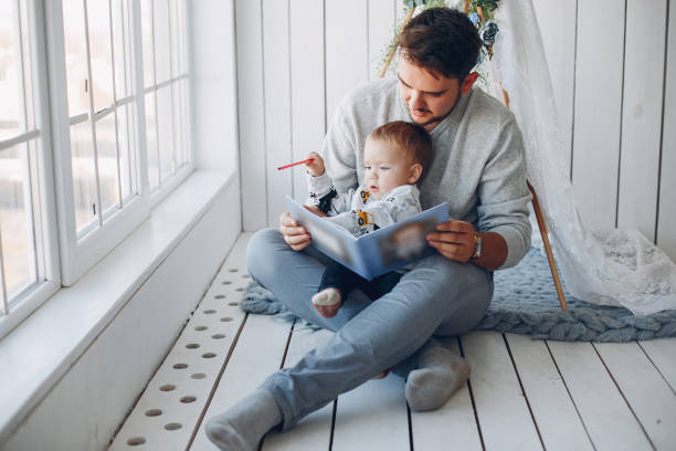 Father sitting at home with little son stock photo