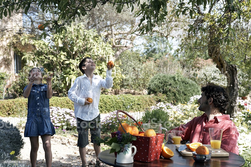 Father sitting at table watching children (8-9) juggling with fruits in garden royalty-free stock photo