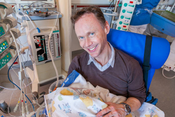 A father sitting on a chair in a intensive care unit holding his sick infant boy wrapped in a blanket surrounded by medical equipment. stock photo