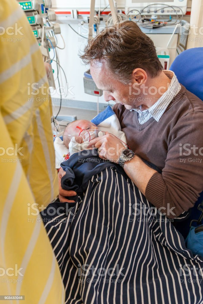 A father sitting on a chair in a intensive care unit holding his sick infant boy wrapped in a blanket surrounded by medical equipment. royalty-free stock photo