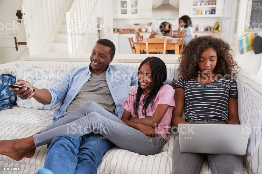 Father Sitting On Sofa Watching TV With Teenage Daughters stock photo