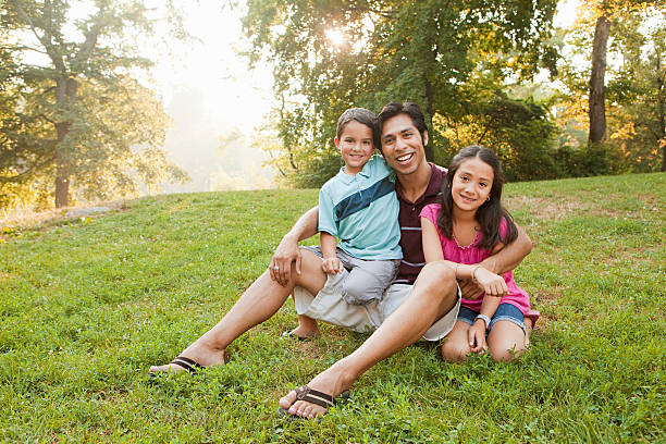 Father sitting with children in park, portrait New York City,USA, indigenous peoples of the americas stock pictures, royalty-free photos & images