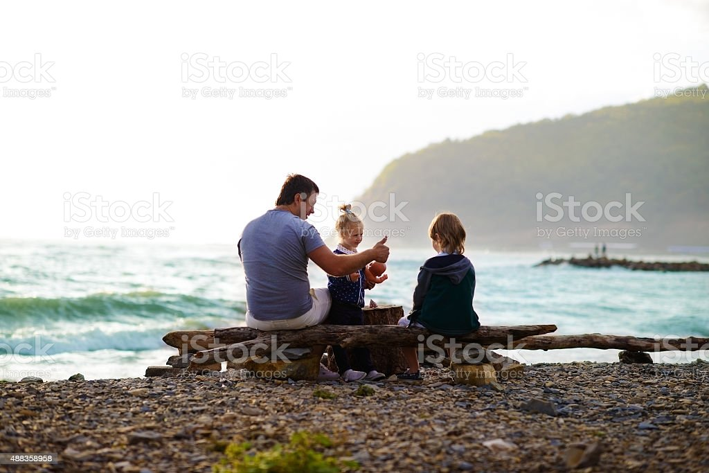 Father sitting with his children on the beach stock photo