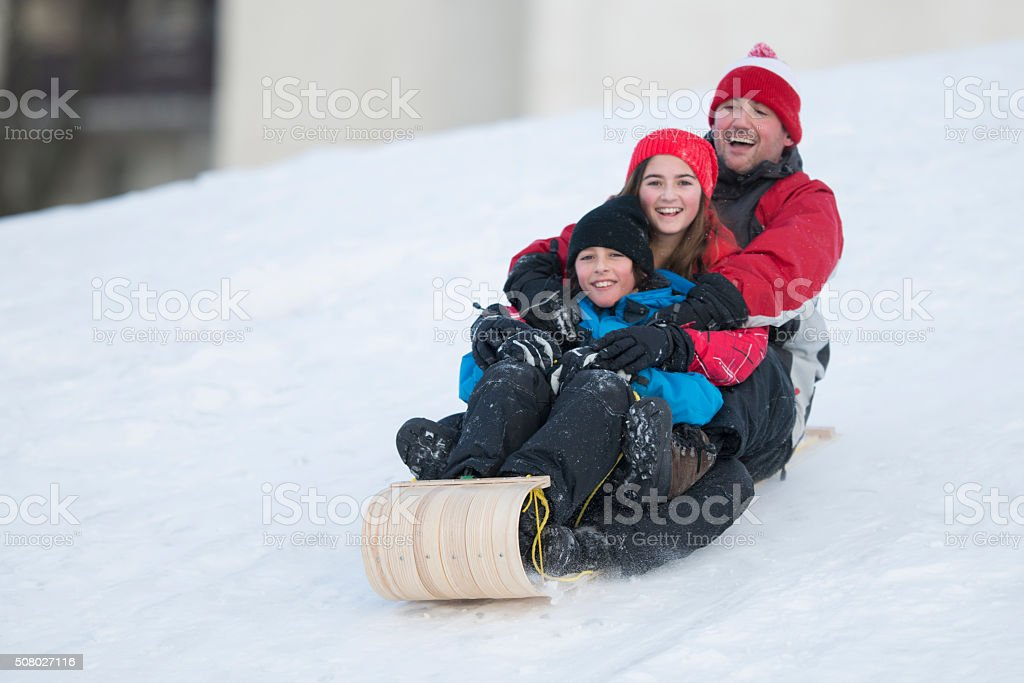 Father Sledding with His Children stock photo