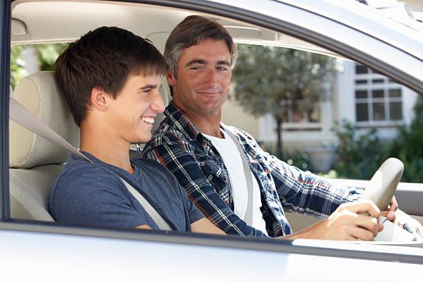 vater lehre teenager sohn zu fahren - autos für fahranfänger stock-fotos und bilder