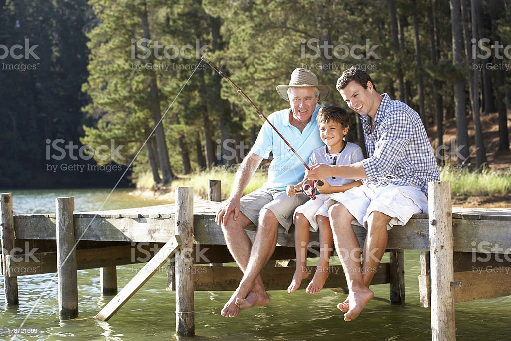 Father, son and grandson fishing together stock photo