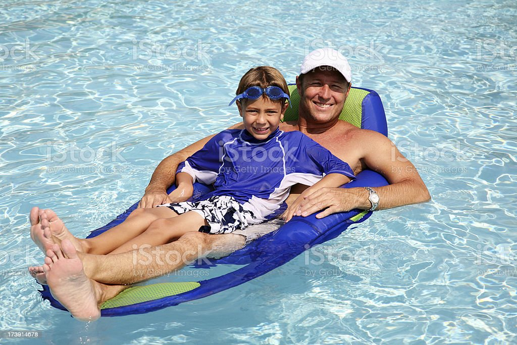 Father Son Floating on Raft in Swimming Pool Summer Vacation royalty-free stock photo