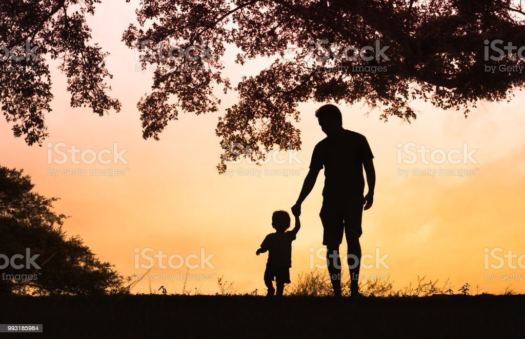 Father son holding hands walking together. stock photo