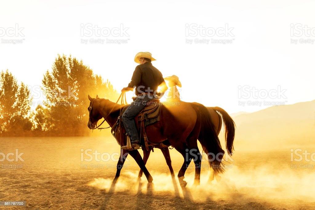 Father Son Horseback Riding in the Utah Country with Early Morning Light stock photo