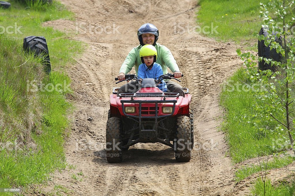 Father & son in helmets riding a quad bike on a track stock photo