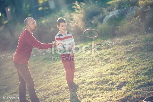 Father Son Playing Hoop and pole (Quoits) or Chunkee game outdoor in the park.