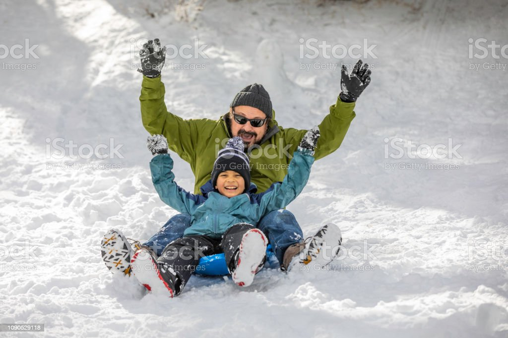 Father Son Sledding Winter Wonderland stock photo
